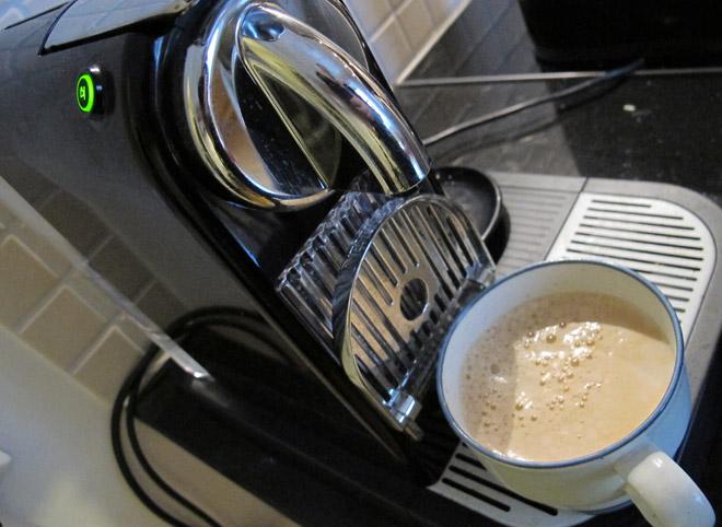 Sitter och sippar på en kopp Nespresso vid datorn.