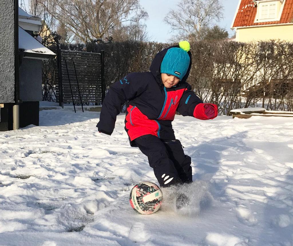Charles dribblar fotbollen genom snön.