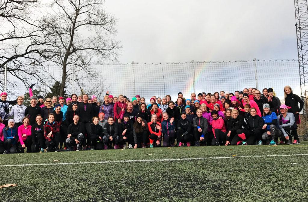 Gruppbild under regnbågen. 100 tjejer på Tjejmilens träningshelg!