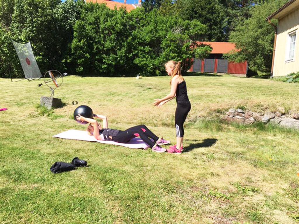 Moa och Linnea tränar mage med boll.